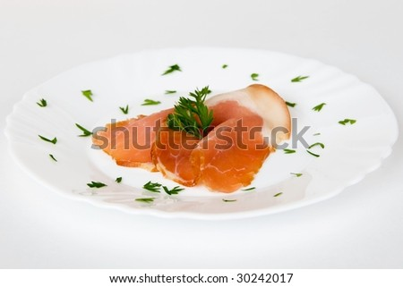 two ham slices on a white plate with green decoration - stock photo