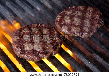 Two Hamburger Patties Cooking on Grill with Flames - stock photo