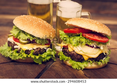 Two hamburgers on the table with beer - stock photo