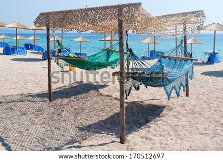 Two hammocks on the sandy beach with umbrellas and sea in the background - stock photo