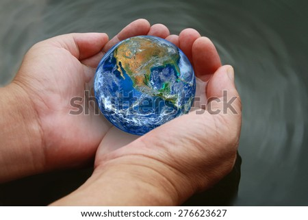 two hand hold the earth on water ,including elements furnished by NASA - stock photo