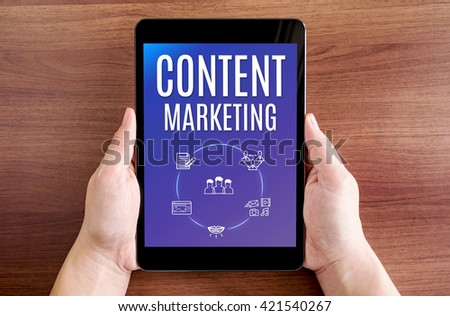 Two hand holding tablet with Content marketing and icon on screen at dark brown table top,Digital business concept. - stock photo