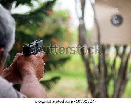 two hand of an unidentified senior male with white hairs holding and shooting black air soft gun model of a replica real pistol in green area in a garden of a country house with fun and serious mood - stock photo