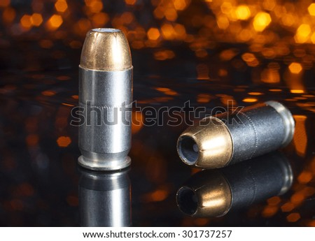 Two handgun cartridges with bullets that are hollow point with an orange background - stock photo