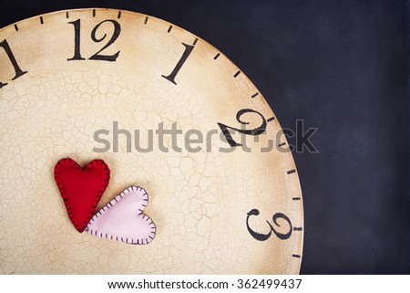 Two handmade stitched hearts on an old vintage clock on a black background - stock photo