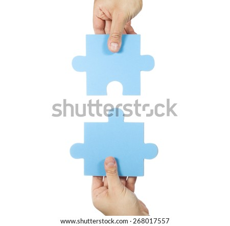 Two hands connecting puzzle pieces - stock photo