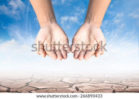 Two hands, cracked earth background. - stock photo