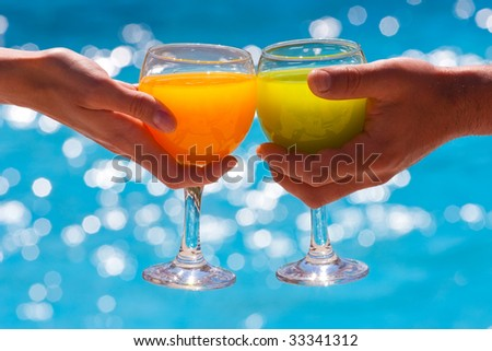 Two hands hold glasses with juice against blue water - stock photo