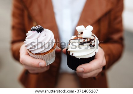 two hands  holding a pink cupcake decorated with hearts, isolated on white background - stock photo