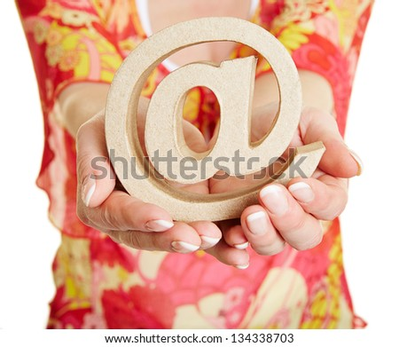 Two hands holding an at sign as symbol for communication - stock photo