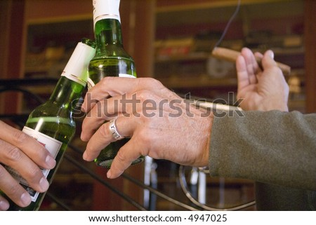 Two hands holding beer - stock photo