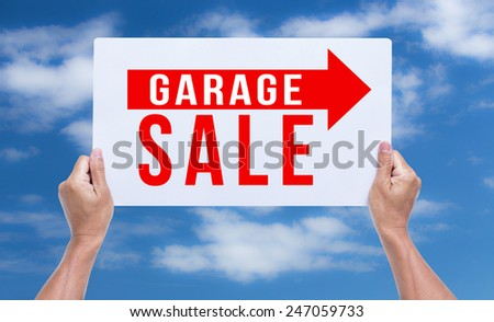 Two hands holding brown cardboard with garage sale on blue sky background - stock photo