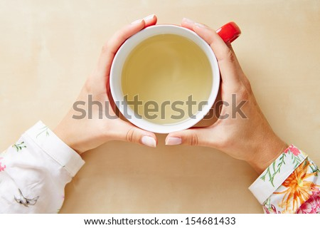 Two hands holding chamomile tea in a cup from above - stock photo