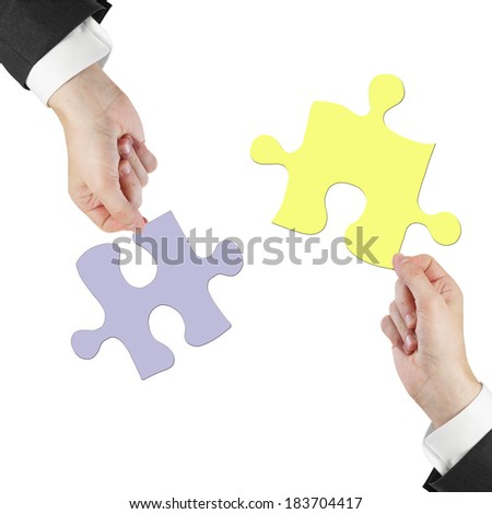 two hands holding puzzle isolated on white - stock photo