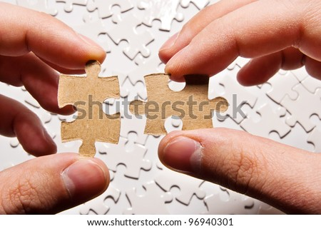 two hands holding puzzle pieces - stock photo