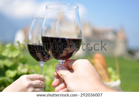 Two hands holding wineglasses against Chateau d'Aigle, Switzerland  - stock photo