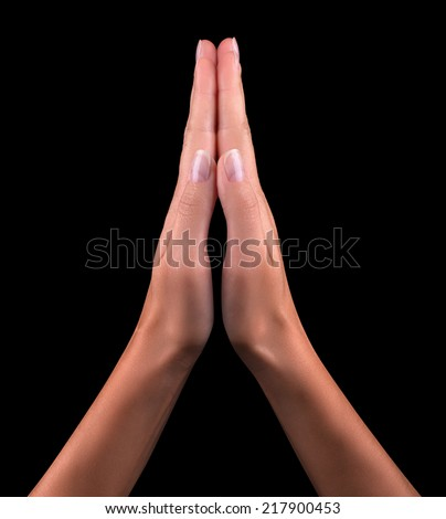 Two hands  isolated on a black background, praying - stock photo