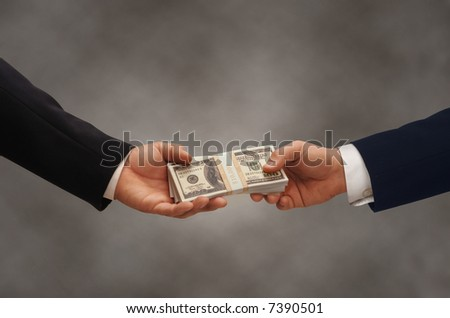 Two hands of businessmen passing a stack of dollars - stock photo