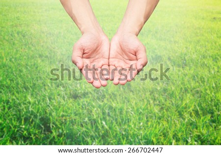 Two hands open palm gesture on blurred nature background - stock photo