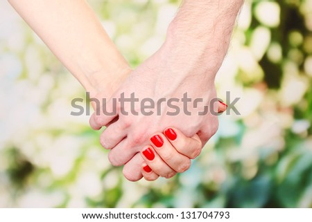 Two hands over green nature park - stock photo