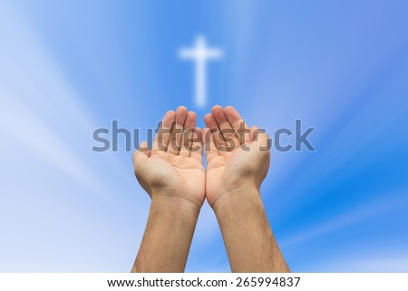 Two hands  pray with cross blurred sky background , soft focused. - stock photo