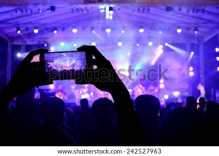 Two hands take photo by smartphone during a concert - stock photo
