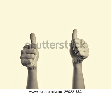 two  hands with a raised thumbs up - stock photo