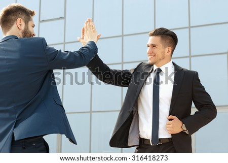 Two handsome business colleagues high fiving outdoors - stock photo