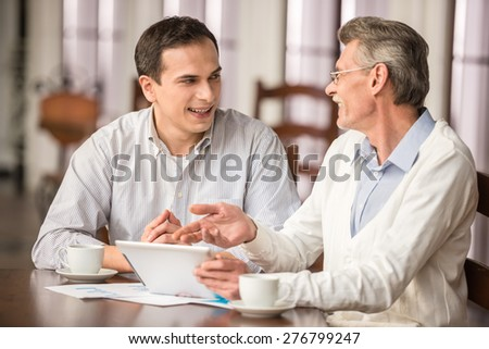 Two handsome businessmen in shirts sitting at the wooden table in urban cafe and talking. - stock photo