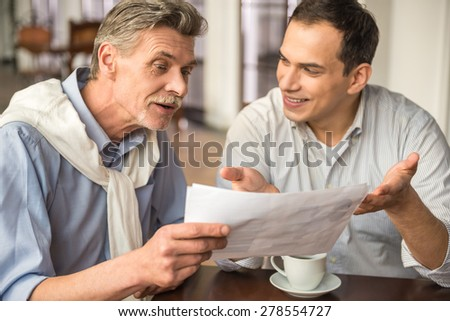 Two handsome businessmen in shirts sitting at the wooden table in urban cafe and working on project. - stock photo