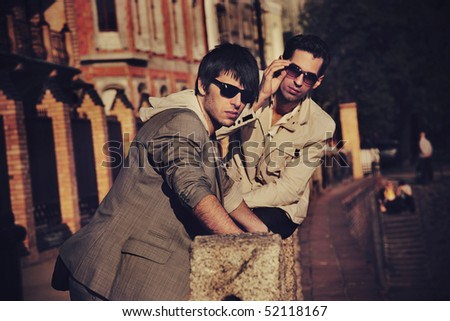 Two handsome friends posing on a city promenade - stock photo