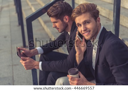 Two handsome young businessmen are using a tablet, talking on the mobile phone and smiling while sitting on stairs of the office building during coffee break - stock photo