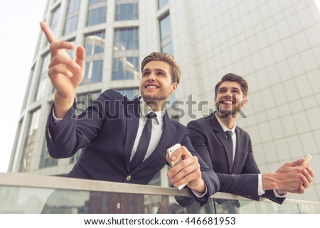 Two handsome young businessmen in classic suits are looking and pointing away, holding phones and smiling, leaning on balcony of the office building - stock photo