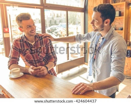 Two handsome young men are using a smartphone, talking and smiling while sitting at bar counter in a modern urban cafe - stock photo
