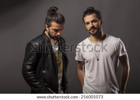 Two handsome young men with a beard and long hair in a bun - stock photo