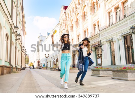 Two happily jumping girls while walking - stock photo