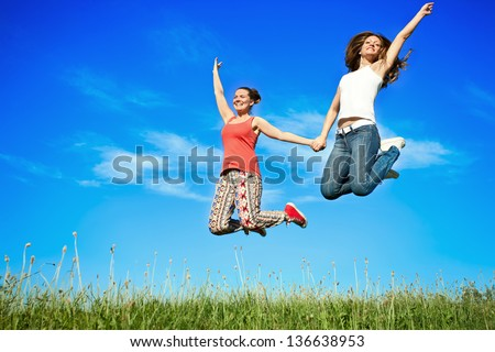 Two happiness young women jumping over blue sky - stock photo