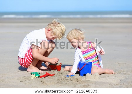 Two happy active children, teenage boy with his little sister, cute blonde toddler girl, playing with plastic toys building sand castles sitting on wide sandy North European beach - stock photo