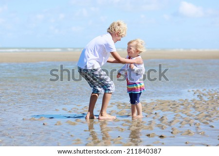 Two happy active children, teenage boy with his little sister, cute blonde toddler girl, playing on sandy beach at low tide, North Sea, Belgian coast - stock photo