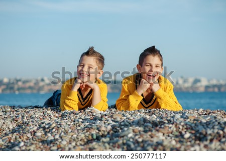 Two happy affectionate young brothers laying on a pebble beach against the sea grinning playfully at the camera - stock photo