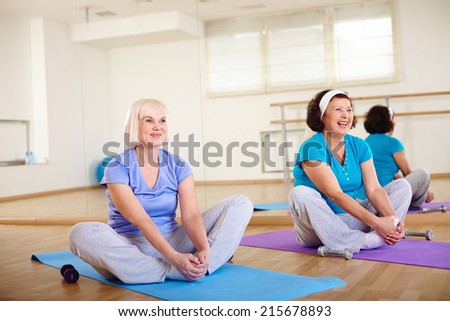 Two happy aged females sitting on mats in sport club  - stock photo