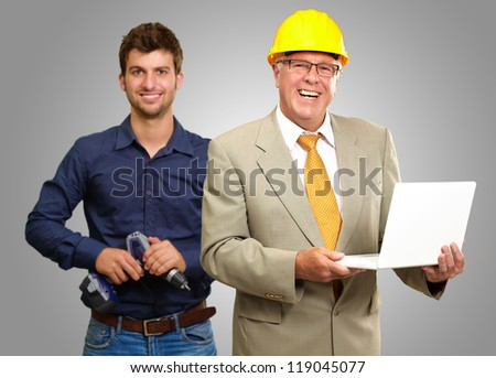 Two Happy Architect Engineers On Gray Background - stock photo
