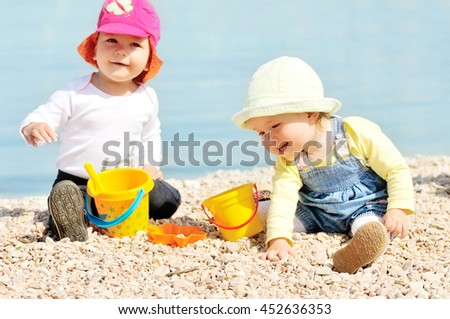 two happy babies playing on the beach - stock photo