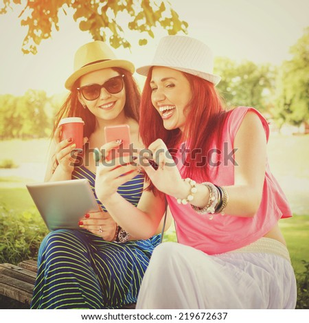 Two happy beautiful young Caucasian women with smart phone and digital tablet outdoors in park on sunny summer day.  - stock photo