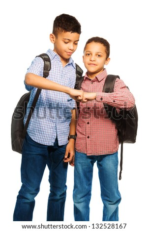 Two happy black brothers standing together with backpack hugging, portrait isolated on white - stock photo