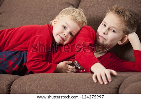 Two happy boys embracing, lying on the sofa - stock photo