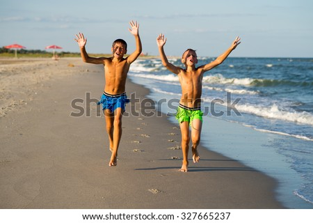 Two happy  boys running on the sea beach at summer. - stock photo