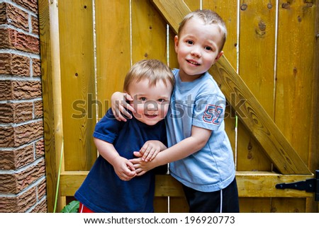 Two happy boys stand together hugging each other.  - stock photo
