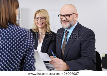Two happy business colleagues, a man and woman, in a meeting sitting smiling as they listen to a second woman with her back to the camera - stock photo