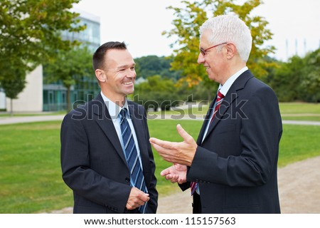 Two happy business people talking with each other in a park - stock photo